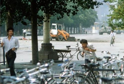 O homem que deteve tanques na praça da Paz Celestial é visto ao fundo, à esquerda; à direita, o impressionante comboio bélico do exército chinês